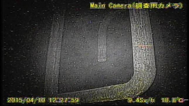 ロボットのカメラがとらえた格納容器内部の様子。右下に「毎時9.4シーベルト」の表示が確認できる(提供:国際廃炉研究開発機構)