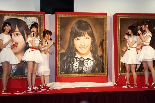 渡辺麻友さんの肖像画に目を丸くするメンバーたち。左から宮脇咲良さん、指原莉乃さん、高橋みなみさん、横山由依さん、柏木由紀さん