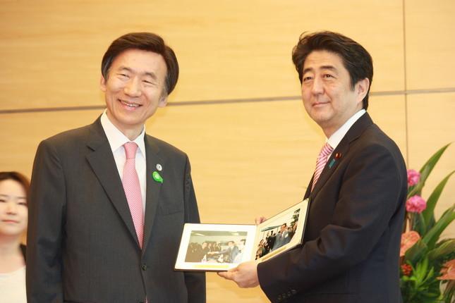 安倍首相と会談する韓国の尹炳世(ユン・ビョンセ)外相(左)。こじれた日韓関係の責任が「日韓双方にある」という論調が韓国メディアでも目立つ(写真:Yonhap/アフロ)