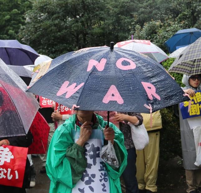 「NO WAR」と書いた傘を差す女性