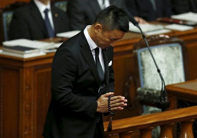 数珠を持ち手を合わせる喪服姿の山本太郎議員(写真:ロイター/アフロ)