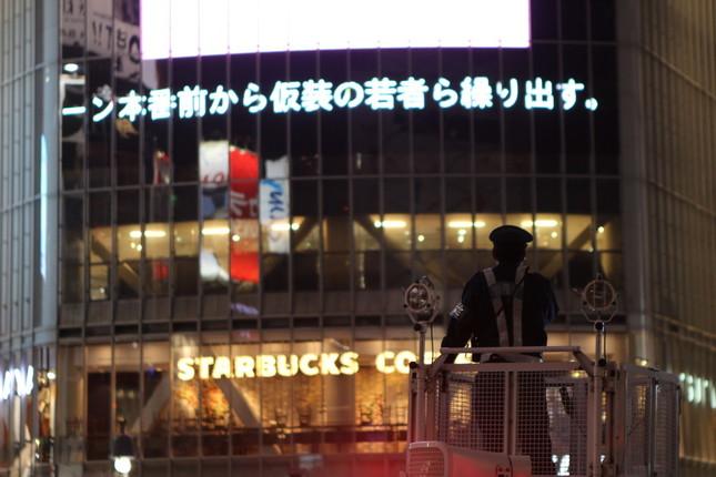 交通整理に当たる「DJポリス」。奇しくも大型ビジョンには、この渋谷のお祭り騒ぎのニュースが流れていた