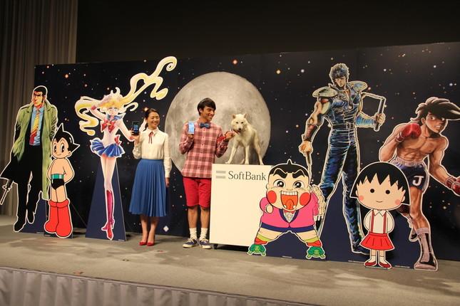 CMは人気アニメの主人公たちがスマートフォンでコミュニケーションを楽しみ「元 セーラームーン」役の小泉今日子さんのバーに集うという設定。(写真はCM発表会の模様。2015年10月撮影)