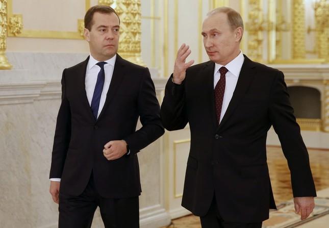 2013年12月12日、ロシアのプーチン大統領(右)がモスクワ・クレムリンでの年次教書演説を終えてメドベージェフ首相と会話を交わす(写真:代表撮影/AP/アフロ)
