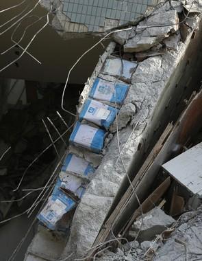 倒壊した建物の柱から見つかった一斗缶が波紋を広げている(写真:AP/アフロ)