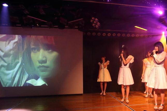 スクリーンに映る高橋みなみさんを見つめる横山由依さん(右)