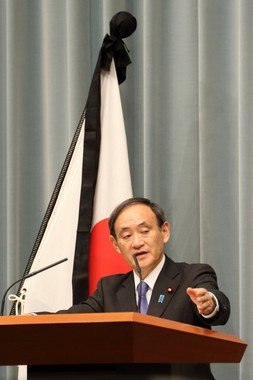記者会見に臨む菅義偉官房長官。東日本大震災発生から丸5年を迎え、背景の日の丸には喪章がついている