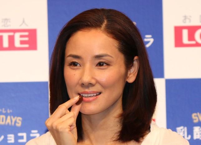 新商品「乳酸菌ショコラ アーモンドチョコレートビター」を口にする吉田羊さん(2016年6月3日撮影)