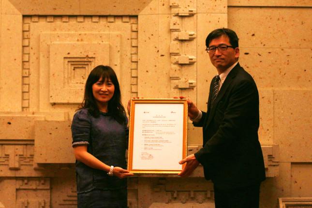 「権利書」を授与。新浪微博国際の総経理Jennie So氏(左)と新浪日本総合ネットワークグループの橘通頼社長(右)