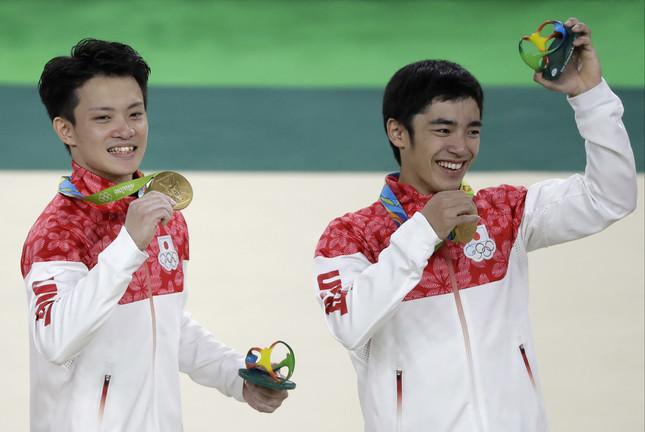 記念品を手にする白井健三選手(右)と田中佑典選手(左)(写真:AP/アフロ)