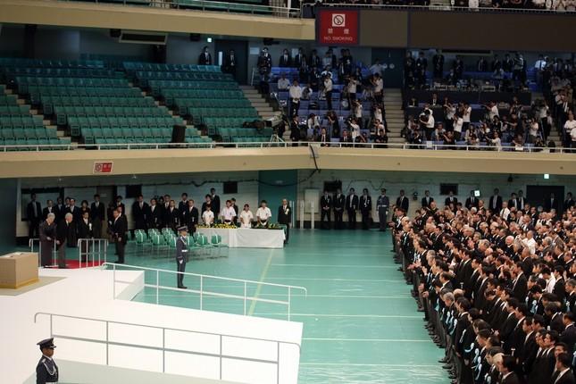 参列者席(写真右)から起こった拍手に見送られる形で、天皇皇后陛下(写真左)は式場を後にした