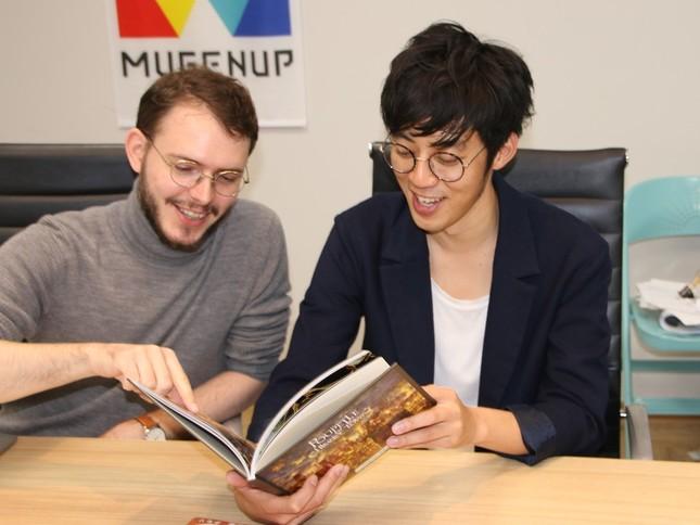 制作統括のペラン・アントワーヌ氏(左)と絵本を眺める