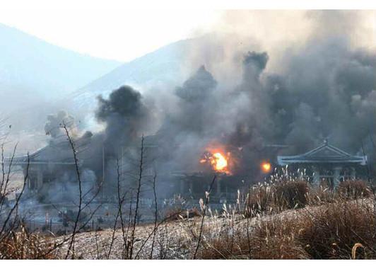 ロケット砲を撃ち込まれて炎上する青瓦台のような建物(「労働新聞」電子版より)