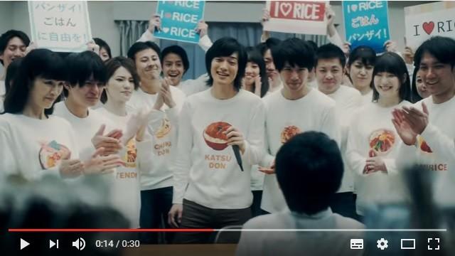 CMの一場面。「バンザイ!ごはんに自由を!」などのプラカードが掲げられ、中央の男性がラップ調コールで扇動する。