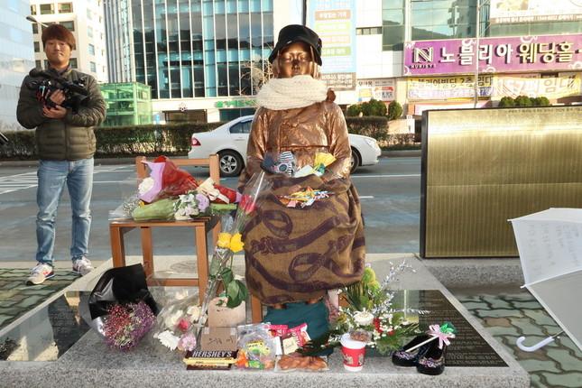 釜山の日本総領事館前に設置された慰安婦像。ストールやマフラーが巻かれ、お菓子や花、靴が備えられている
