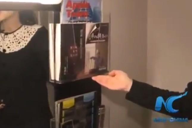 新華社通信が配信した「現地取材」の動画。アパホテルの室内で問題の書籍を発見する場面