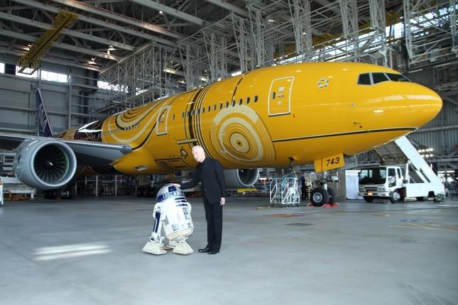 「C-3PO ANA JET」を背景に取材に応じるアンソニー・ダニエルズさん。横に並んでいるのが「R2-D2」だ
