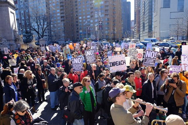 愛国歌「アメリカ・ザ・ビューティフル」を歌う人たち。大勢の反トランプ派に交じり、 左後方に「BUILD THE WALL」のボードを持ったトランプ派も見える。
