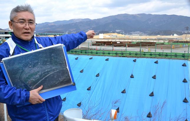 震災当時の津波被害を説明する河野正義さん。写真右奥に「奇跡の一本松」が見える