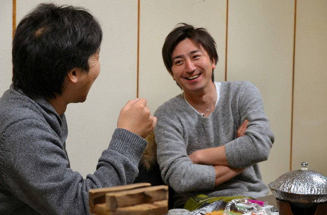 管野さんと食事を囲みながら話す菊地基文さん(写真右)