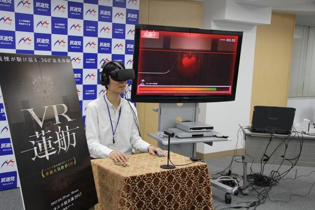 VR蓮舫を体験するJ-CASTニュース記者。中央のディスプレーに心拍数に応じて減少するゲージが表示されている