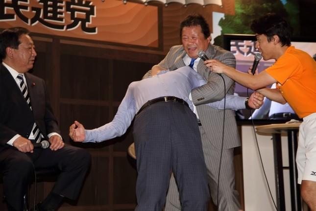 必殺技「ドラゴンスリーパー」をかけられる大西健介衆院議員(中央)