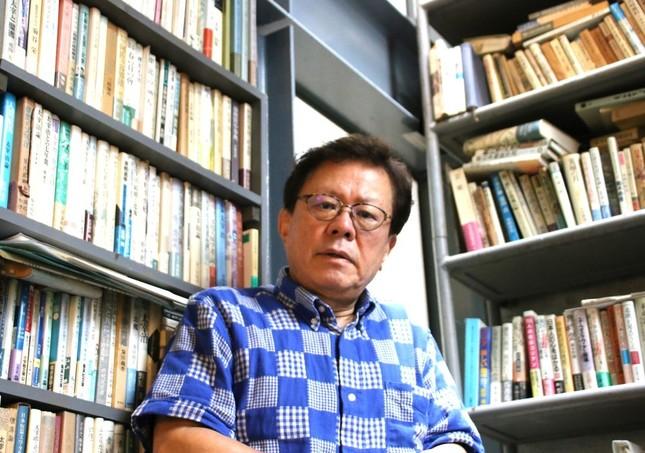 自身のオフィスの書棚の前に立つ猪瀬直樹氏。書棚の高さは10メートルにもなる