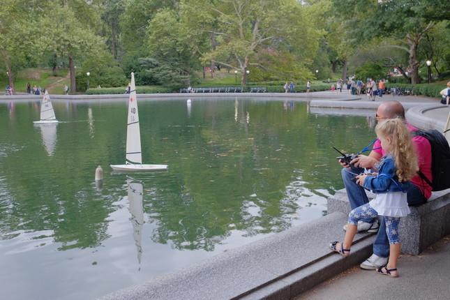 ニューヨークのセントラルパークの池で遊ぶ親子