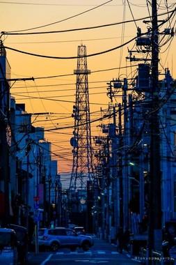 「tokyopasserby」(@tokyopasserby)さんの投稿した写真。夕暮れの街に、電柱と鉄塔がそびえる