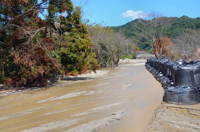 川の水はいまだに濁った色のまま。水害対策に土嚢が積まれていた