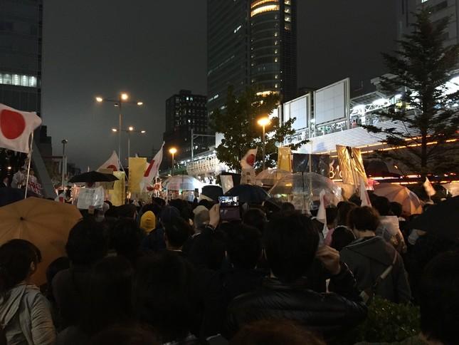 10月21日夜のJR秋葉原駅前。写真中央で白く光る選挙カーの上に、安倍氏らが立っている