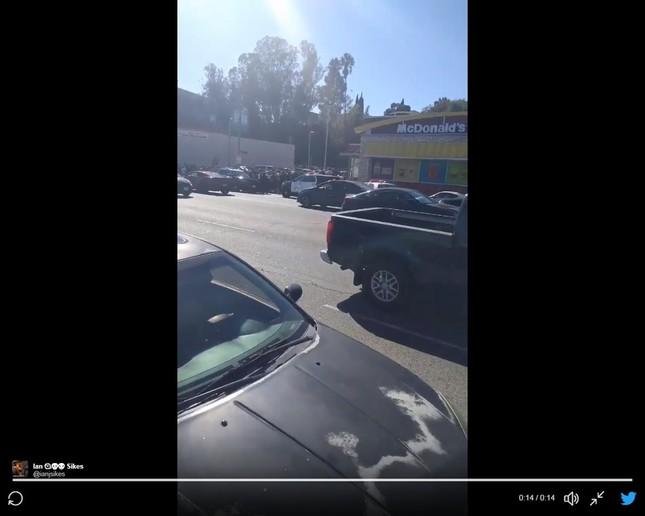 @ianjsikesさんがツイッターに投稿した動画。「四川風ソース」を求める群衆や警察の車がうつっている。
