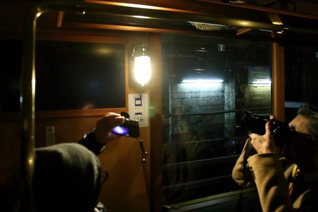 車内が一瞬だけ停電して補助灯がつく様子。乗客は熱心に写真に収めていた
