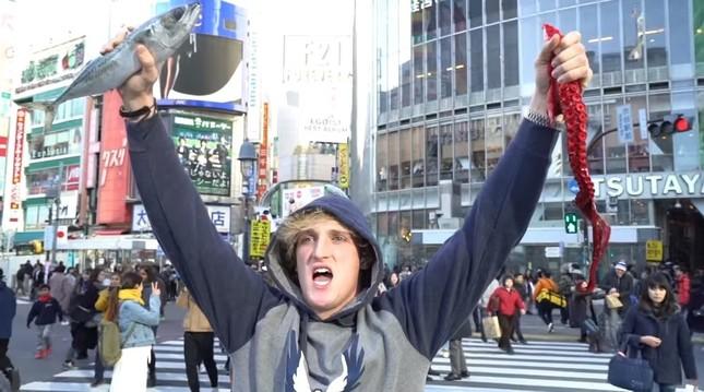 渋谷のスクランブル交差点でタコの脚と魚を手に「イエーイ!!」。再生回数は570万回を超えている(ポール氏の動画から)