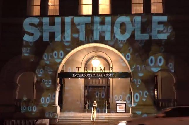 トランプ・インターナショナル・ホテルの正面に浮かび上がった「SHITHOLE」とウンコの形の笑顔の絵文字。2018年1月13日、ワシントンで。(Sorane Yamahira /  http://Bellvisuals.com)