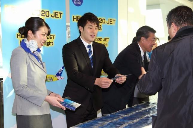 瀬戸大也選手は記念品を渡しながら初便の搭乗客を見送った