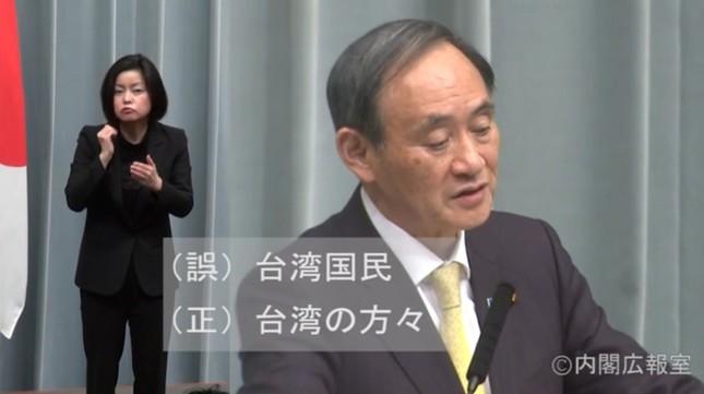 記者会見で台湾へのお見舞いメッセージについて答弁する菅義偉官房長官。「(誤)台湾国民 (正)台湾の方々」という訂正のテロップが入った