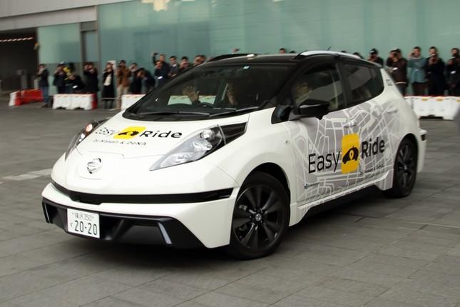 実証実験は日産電気自動車「リーフ」をベースにした実験車で行う。運転席の男性がハンドルから手を離しているのが分かる