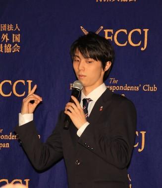 会見場で立ち上がり、身振り手振りで4回転アクセルの説明をする羽生選手(東京・有楽町の日本外国特派員協会で)