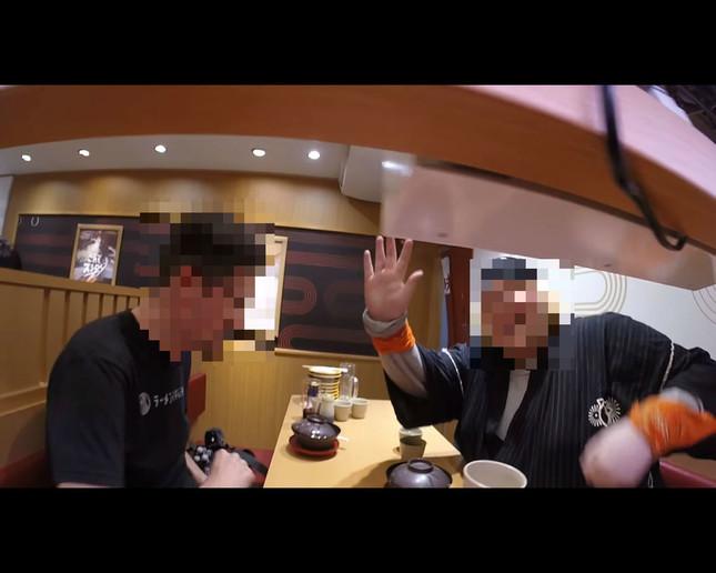 手を振ってレール上のカメラを見送るYouTuber(画像は問題の動画より、編集部で一部加工)