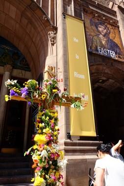 2017年の復活祭の日。ニューヨーク市マンハッタンの五番街の教会前に大きな十字架が掲げられ、道行く人々に配られる生花が飾ってあった