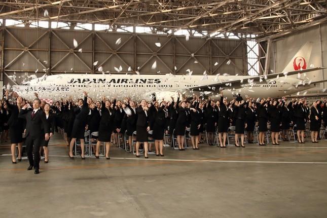 「テイクオフ!」の掛け声でいっせいに紙飛行機を飛ばした。写真左が赤坂祐二社長