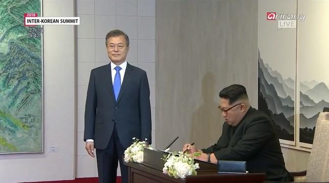 韓国で話題になった場面。サインする金正恩氏を文在寅氏が待っている