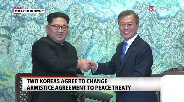 「板門店宣言」に署名する両首脳。「完全な非核化」を目指すとした(画面は韓国・アリランテレビから)
