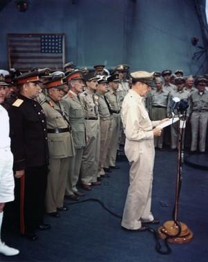 ミズーリ号上で行われた無条件降伏文書調印式でスピーチする連合軍最高司令官のダグラス・マッカーサー元帥。背後には「黒船来航」時の星条旗が飾られている