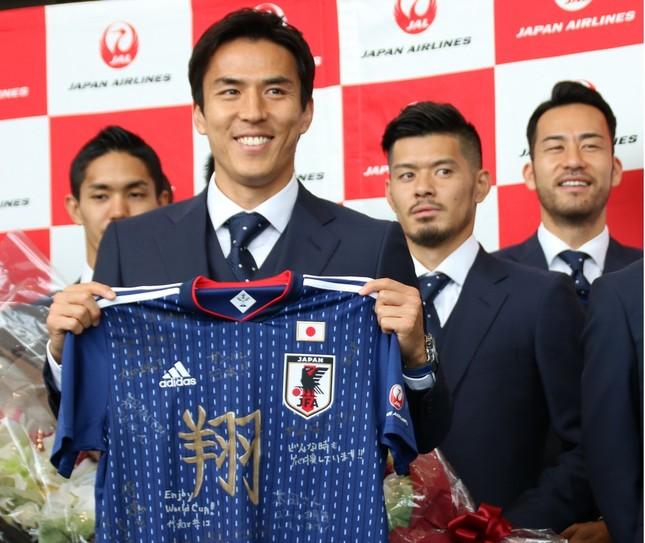 メッセージ入りのユニフォームを受け取り笑顔の主将・長谷部誠選手(左から2人目)