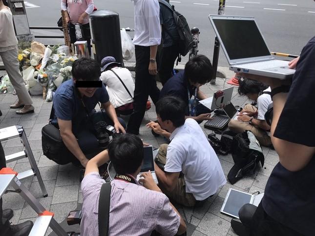 献花台の前で座り込む記者陣(湯島のとも@Syasさん提供、画像は編集部で一部加工)