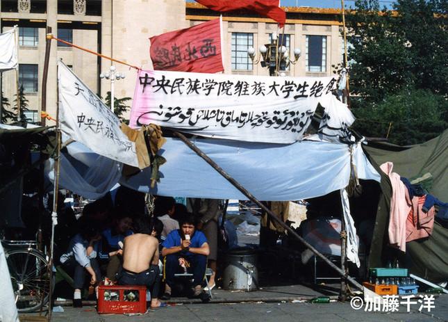 天安門広場の中央民族学院テントの横幕。漢字とウイグル文字で「維族(ウイグル族)大学生ハンスト」とある (1989年5月、加藤千洋氏撮影)