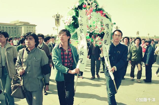 天安門広場の人民英雄記念碑に追悼の花輪をささげる王丹=左。89年4月17日、加藤千洋氏撮影