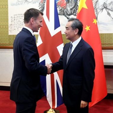 英国のハント外相(左)と中国の王毅外相(右)(写真は中国外務省ウェブサイトから)